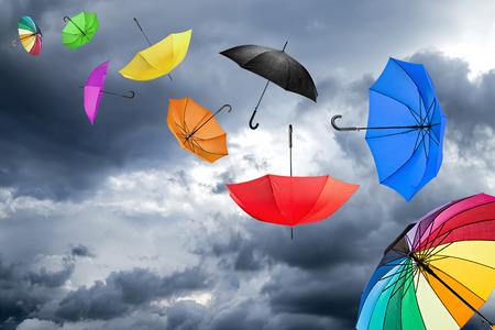 дождь: летать зонтики перед темном небе Фото со стока