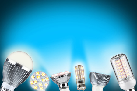 energy conservation: row of different types of glowing light bulbs