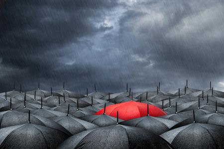 arm met rode paraplu in de massa van zwarte paraplu's
