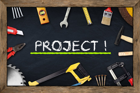 tools on project blackboard with wooden frame photo