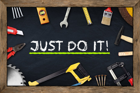 tools on just do it blackboard with wooden frame photo