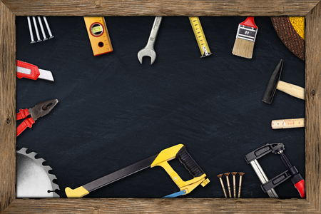 tools on blackboard with wooden frame photo
