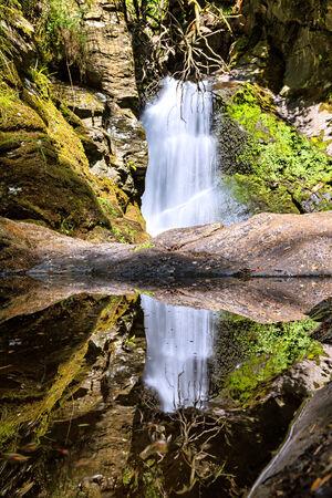 reflektion: wassefall mit reflektion in einer Pfütze Stock Photo