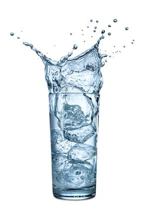 水の入ったグラスに氷水しぶき 写真素材
