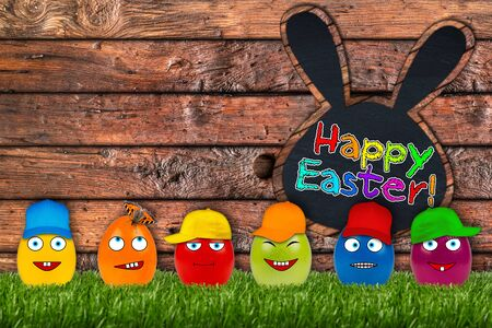 funny eater eggs in front of wooden easter background photo