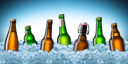 氷の上の緑と茶色のビール瓶