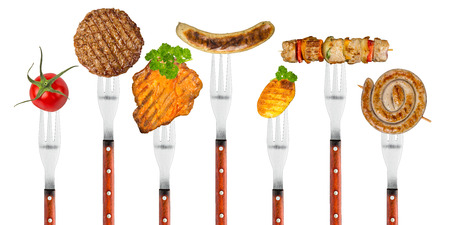 chorizos asados: fila de tenedores con comida a la parrilla Foto de archivo