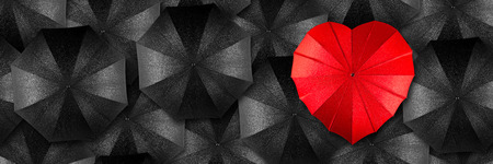 red heart shaped umbrella in middle of black umbrellas Standard-Bild
