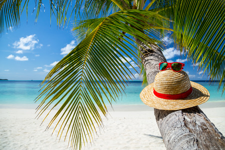 straw hat with sunglasses in front of paradise beach Stock Photo