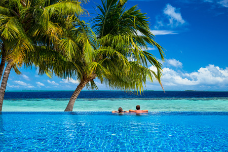 young couple relaxing in infinity pool under coco palms in front of tropical  landscape