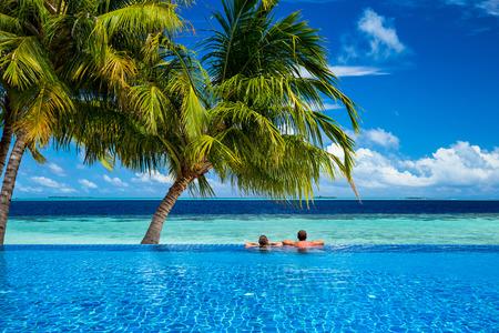 parejas: joven pareja relajarse en la piscina de borde infinito bajo las palmas de coco en la parte delantera del paisaje tropical