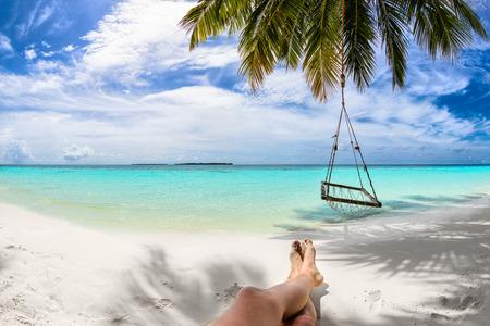 pies masculinos: los pies de arena en la playa bajo la palma de coco Foto de archivo