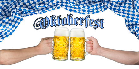 stein: cheers! hands holding up german beer mugs under bavarian flag
