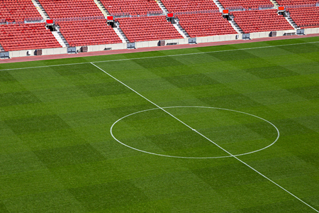sports shell: empty soccer stadium with red seat shells and green field Stock Photo