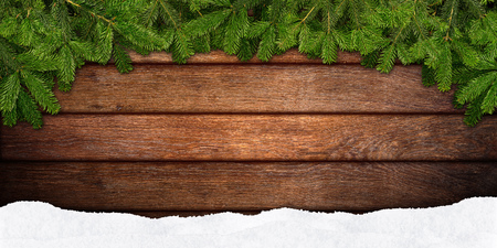 christmas tree branch: fir branches and snow on wooden background