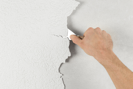 plaster removal with hand and spatula Stock Photo