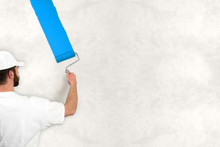 priming brush: young man painting wall with blue color