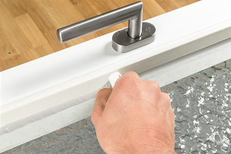 skirting: renewing of a silicone joint on a window Stock Photo
