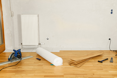 wood flooring: empty flat with parquet flooring and tools