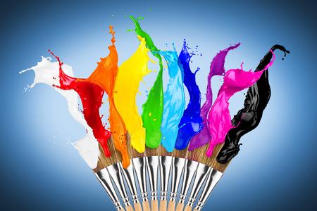 kleurrijke kleur spatten penseel rij geïsoleerd op een blauwe achtergrond Stockfoto