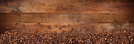 コーヒー豆をその広い素朴なオークの背景 写真素材