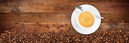 coffee cup and beans on wide rustic oak background