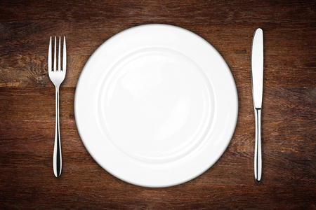 place setting with empty dish fork and knife on wooden background