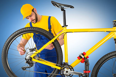 brake caliper: bicycle mechanic mounting brake caliper on yellow mountain bike