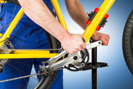 pedal: bicycle mechanic tightening pedal on mountain bike Stock Photo