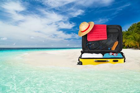 suitcase on paradise beach with crystall clear ocean