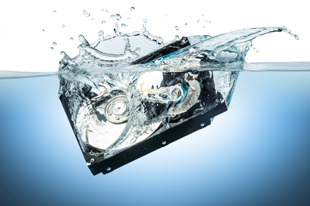hard drive crash: hard disc drive splashes into water Stock Photo