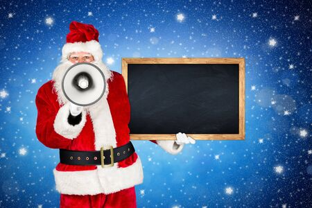 traditional classic red white santa claus making shouting loud announcement with bullhorn megaphone wooden blackboard in his other hand in front of holy night blue stars sky background Stock Photo