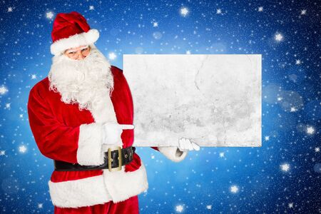 traditional classic red white santa claus making pointing with his finger on concrete stone billboard in his other hand isolated front of blue night sky stars background
