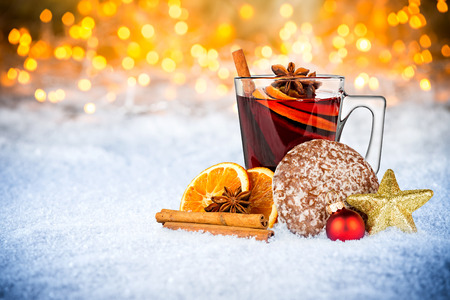 hot mulled spiced red wine in glass mug with gingerbread orange slice christmas xmas decoration illuminated bright lights bokeh background Stock Photo