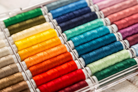 coser: box with colorful sewing cottons spools on wooden table