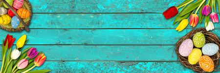 bunter hölzernes Ostern Hintergrund Tulpen türkis Textur auf rustikale alte Eiche Eier Nest Korb blau Holz