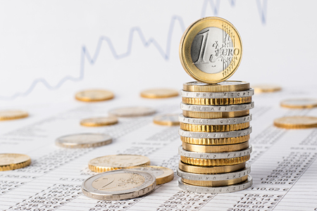finance business accounting stock background with stack of euro coins on data sheet