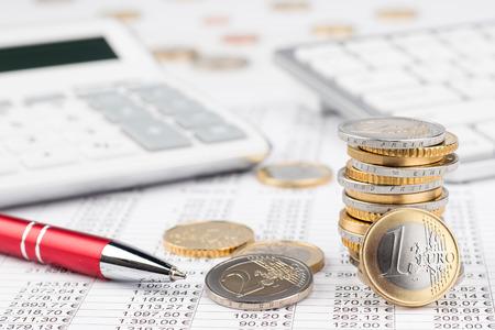fondo di riserva di contabilità di affari di finanza con la pila di euro monete calcolatrice e tastiera rosse della penna sulla scheda di dati