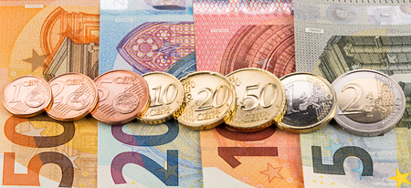 row of all euro cent coins on bank notes wide panorama finance background
