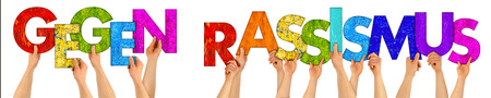 tolerancia: translation Gegen Rassismus  against racism hands holding up colorful wood letter isolated on white background tolerance refugee concept