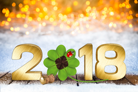 happy new years eve silvester golden 2018 number with four-leaf clover and ladybug in front of bright bokeh background on snow Stock Photo