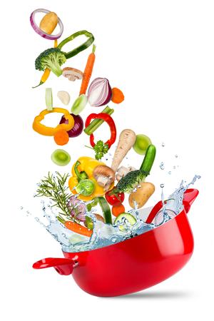 verse ingrediënten vallen vliegen in rode kookpot met water splash creatief koken concept geïsoleerd op een witte achtergrond Stockfoto