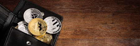 crypto currency coin in black leather wallet on wide wood wooden panorama background with copy space bitcoin ethereum litecoin iota ripple