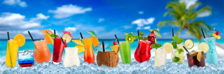 row of various colorful cocktails and long drink beverages in crushed ice cubes isolated on tropical palm beach ocean paradise background Standard-Bild