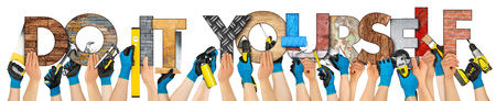hand with tools and diy do it yourself handyman lettering concept isolated on wide panorama background Stock Photo