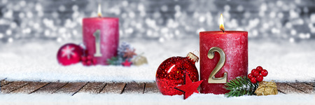 second sunday of advent red candle with golden metal number one on wooden planks in snow front of silver panorama bokeh background