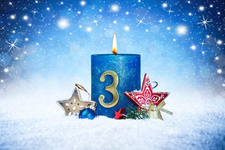 third sunday of advent blue candle with golden metal number red decoration one on wooden planks in snow front of silver panorama bokeh background