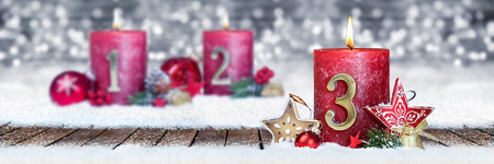 third sunday of advent red candle with golden metal number one on wooden planks in snow front of silver panorama bokeh background Stok Fotoğraf