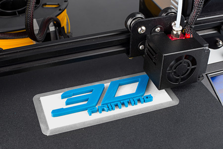 3d print of printer printing logo symbol lettering with white blue pla filament modern future technology concept background Standard-Bild