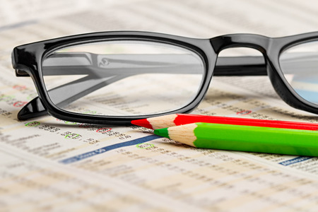 glasses red green pen pencil on newspaper with stock market exchange data chart finance business concept cash background Banco de Imagens